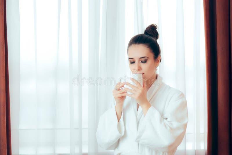 Kvinna i startande morgon för badrock med en kopp kaffe fotografering för bildbyråer