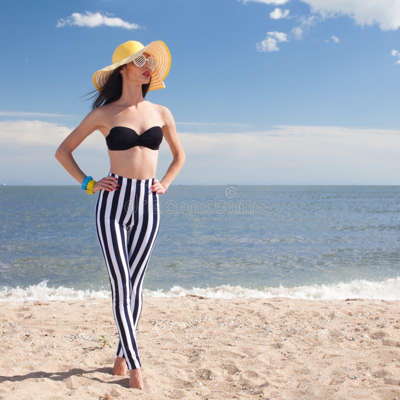 Kvinna i stilfull baddräkt på stranden royaltyfri foto
