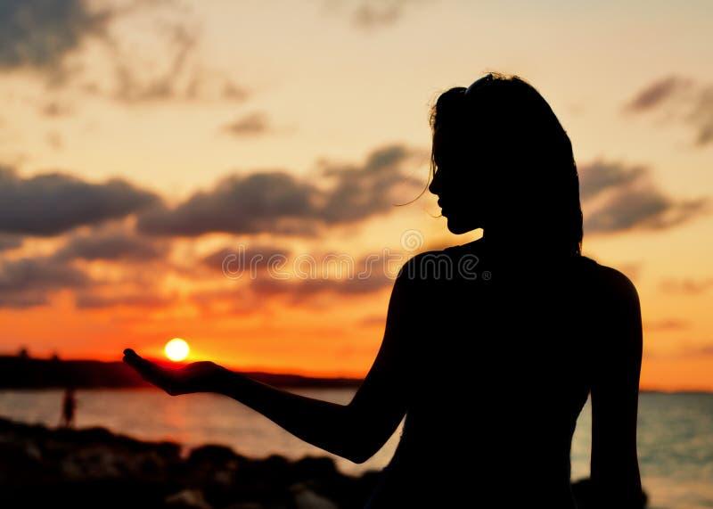 Kvinna i stranden på solnedgången royaltyfri foto