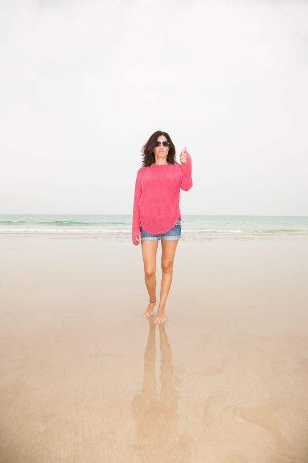Kvinna i strandfingerok royaltyfri foto