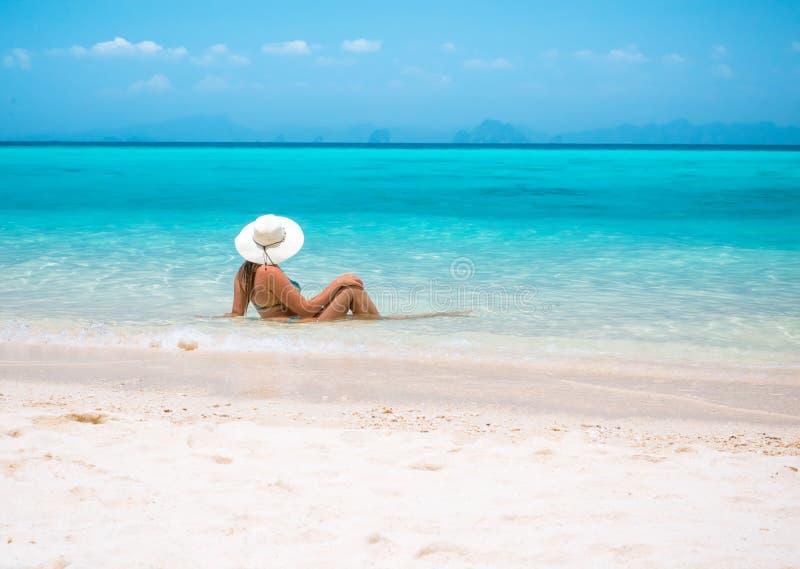 Kvinna i sugrörhatt som vilar den tropiska Thailand stranden arkivfoto