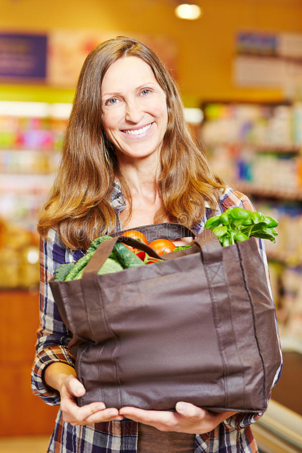 Kvinna i supermarketinnehav arkivbild
