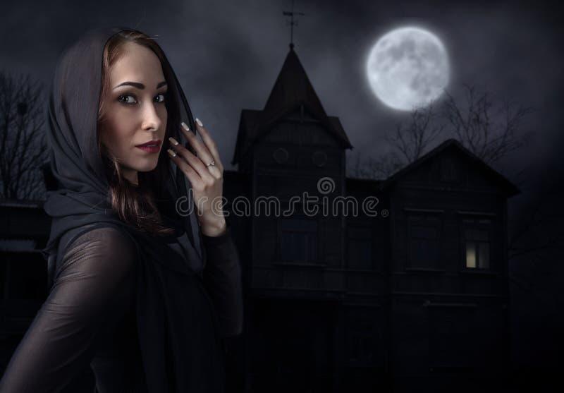Kvinna i svart framme av det gamla huset på en månbelyst natt royaltyfri bild