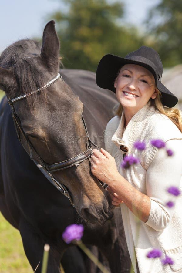 Kvinna i svart hatt som slår hennes häst royaltyfria foton