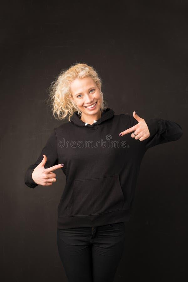 Kvinna i svart hoodie som pekar med båda händer på den royaltyfri foto