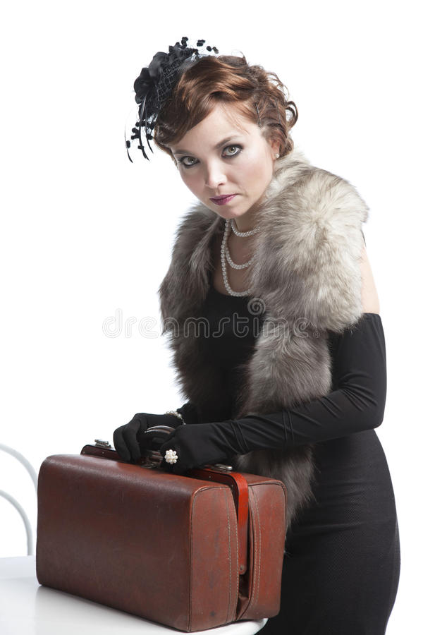 Kvinna i svart klänning med resväskan royaltyfri bild