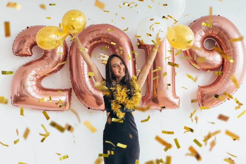 Kvinna i svart klänning och gul krona som firar nytt år och att ha gyckel, dans fotografering för bildbyråer