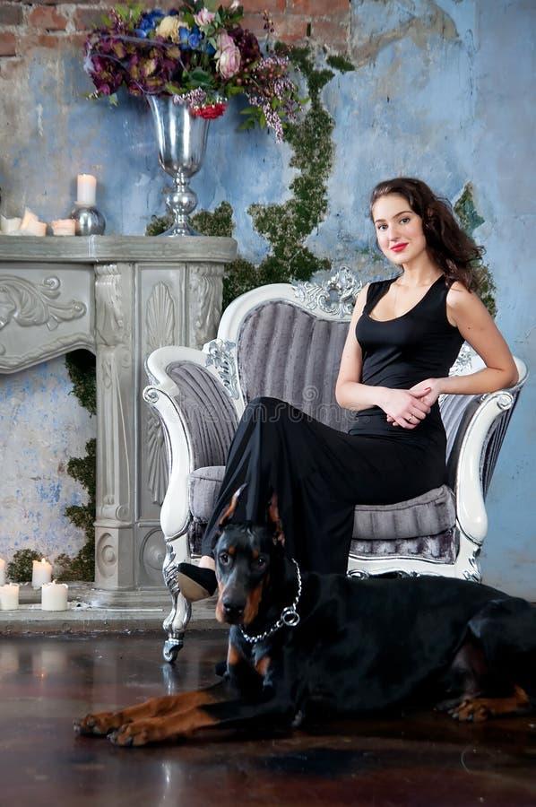 Kvinna i svart långt klänningsammanträde på stol med hunden (dobermanen) royaltyfria bilder