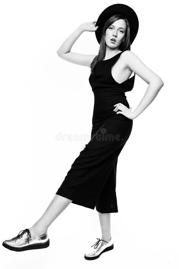 Kvinna i svart overall och hatt royaltyfri foto