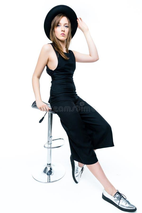 Kvinna i svart overall och hatt arkivbild
