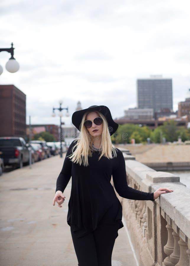 Kvinna i svart på stadsgatan arkivfoto
