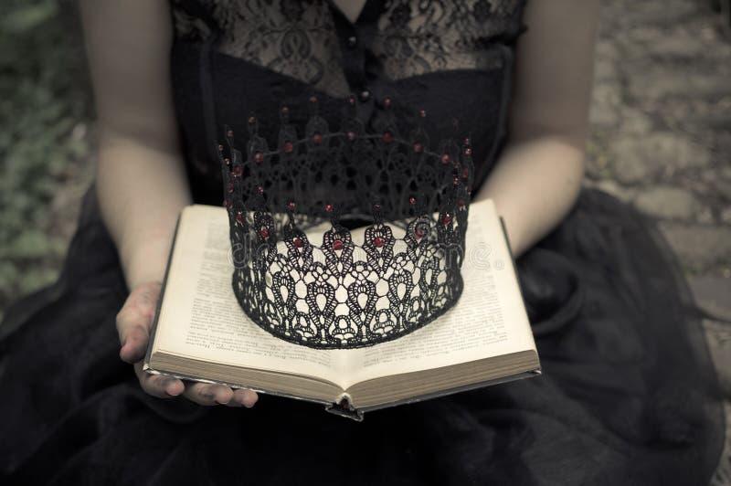 Kvinna i svarta klänninginnehav en bok och en krona arkivfoto