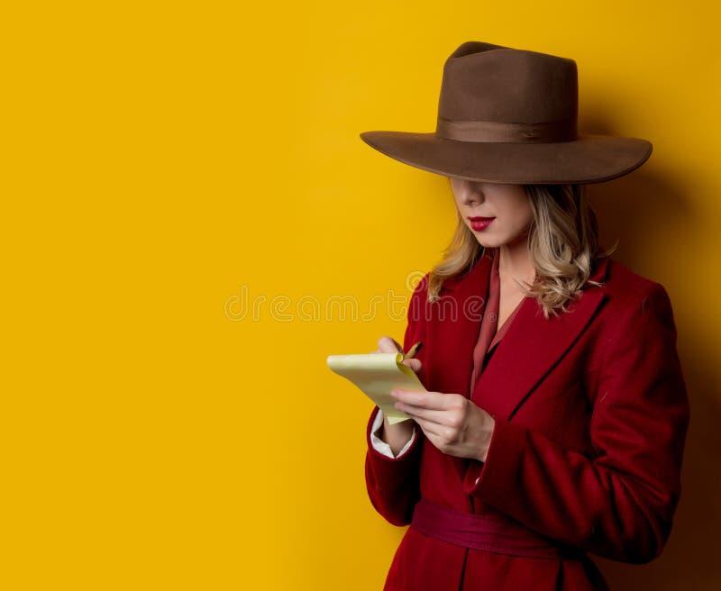 Kvinna i 40-talstilkläder med anmärkningen och pennan arkivbilder