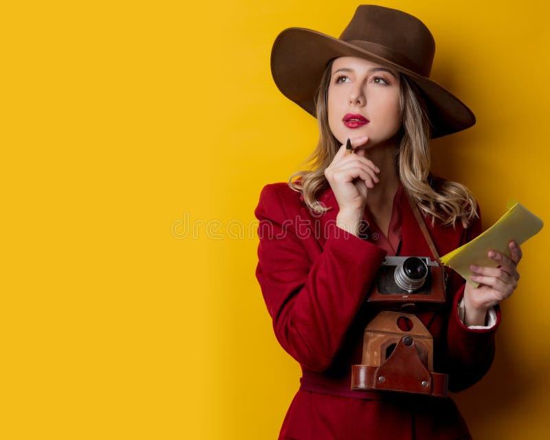 Kvinna i 40-talstilkläder med anteckningsboken och pennan royaltyfria bilder