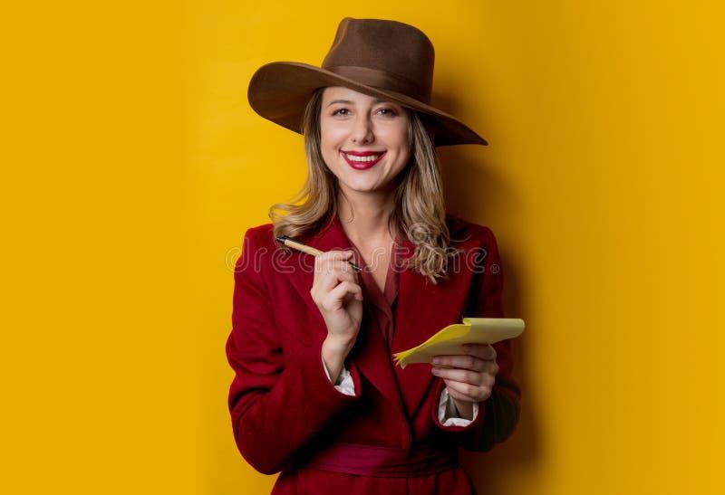 Kvinna i 40-talstilkläder med anteckningsboken och pennan fotografering för bildbyråer