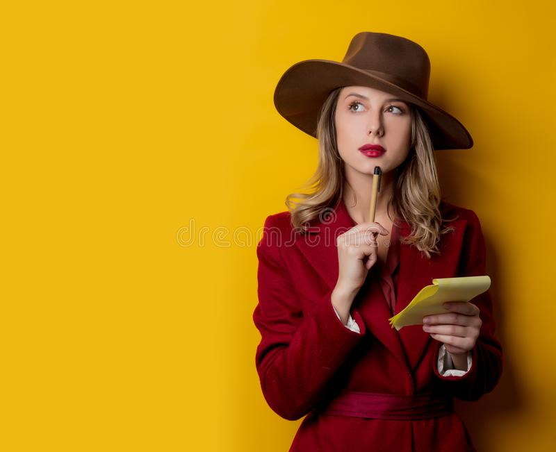 Kvinna i 40-talstilkläder med anteckningsboken och pennan arkivbild