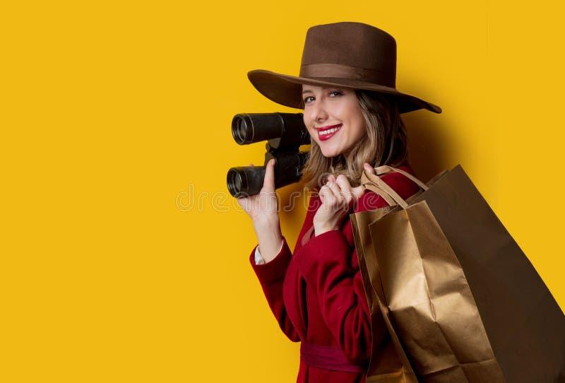 Kvinna i 40-talstilkläder med kikare och påsar arkivfoto