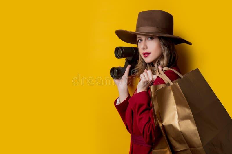 Kvinna i 40-talstilkläder med kikare och påsar arkivfoton