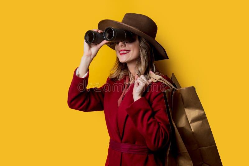 Kvinna i 40-talstilkläder med kikare och påsar arkivbilder