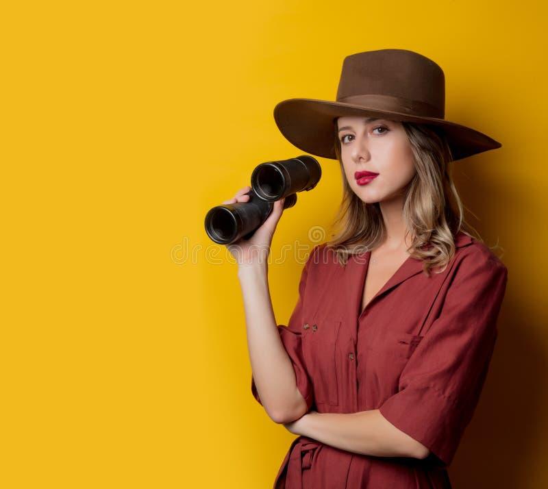 Kvinna i 40-talstilkläder med kikare arkivfoto