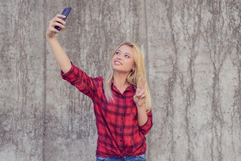 Kvinna i tillfällig kläder med att stråla taling selfie för leende på henne royaltyfri bild