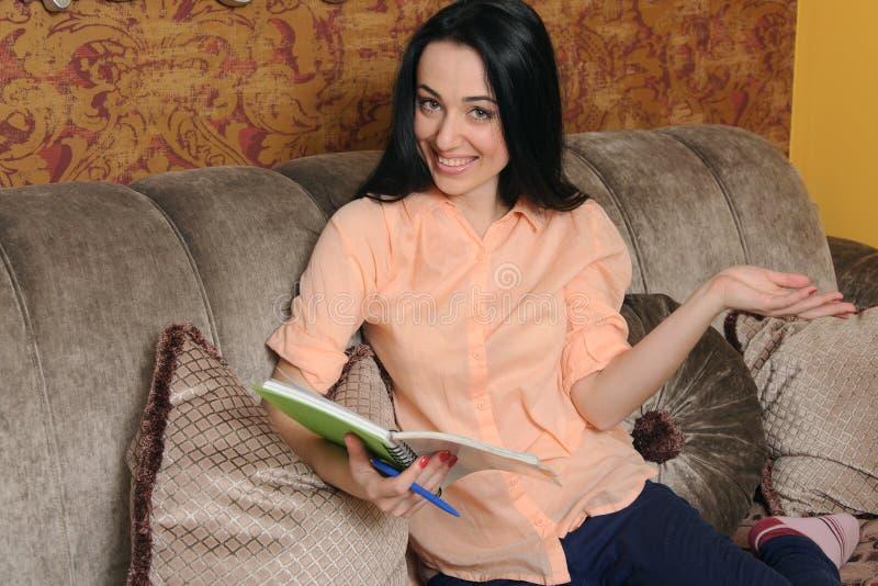 Kvinna i tillfällig kläder som sitter med en anteckningsbok arkivbild