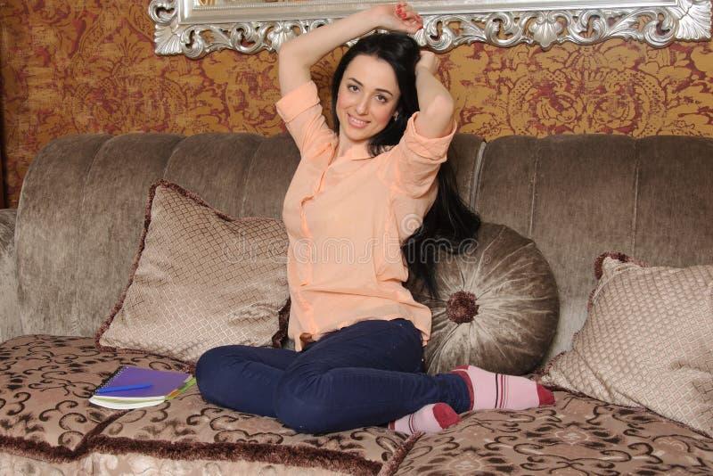 Kvinna i tillfällig kläder som sitter på en soffa och elasticiteter arkivfoto