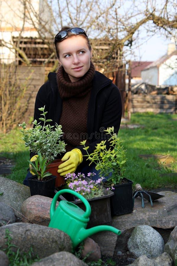 Kvinna i trädgård arkivbild