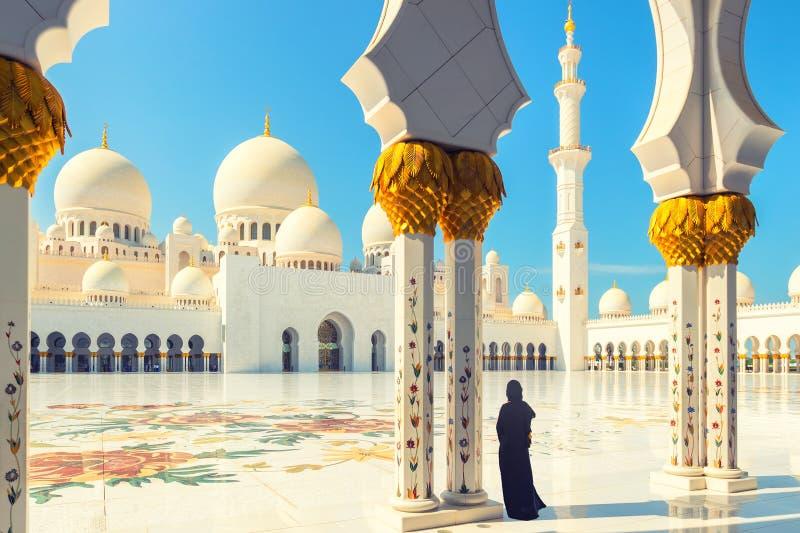 Kvinna i traditionell klänning inom Sheikh Zayed Mosque – turist- bärande svart abaya som besöker den berömda arabiska religiösa  arkivfoton