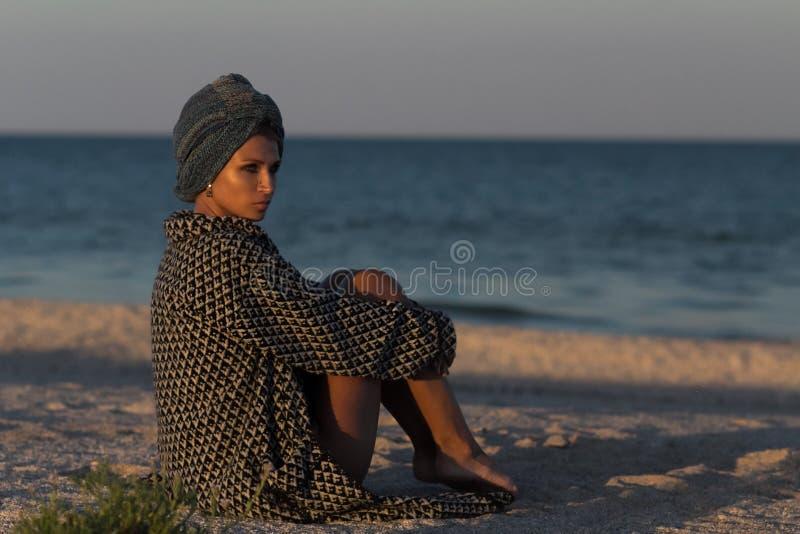 Kvinna i turbanen och laget som sitter på den sandiga havsstranden royaltyfri foto