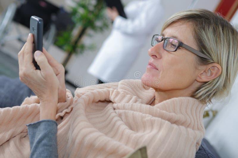 Kvinna i väntande rum för sjukhus genom att använda telefonen royaltyfri bild