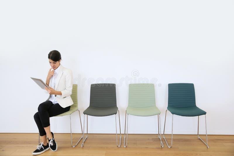 Kvinna i väntande rum genom att använda den digitala minnestavlan arkivfoto