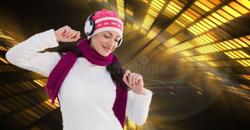 Kvinna i varma kläder som lyssnar till musik till och med hörlurar arkivfoton