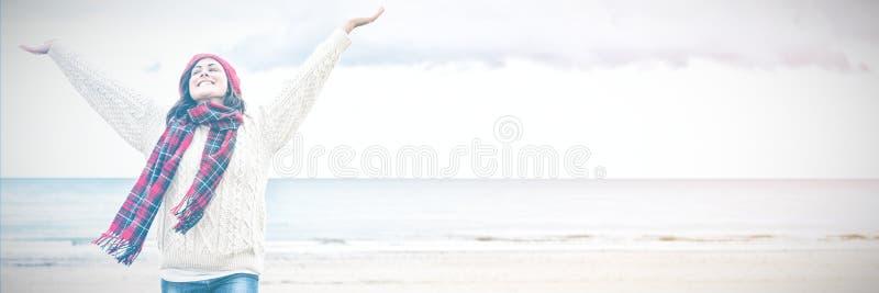 Kvinna i varma kläder som sträcker armar på stranden arkivbilder