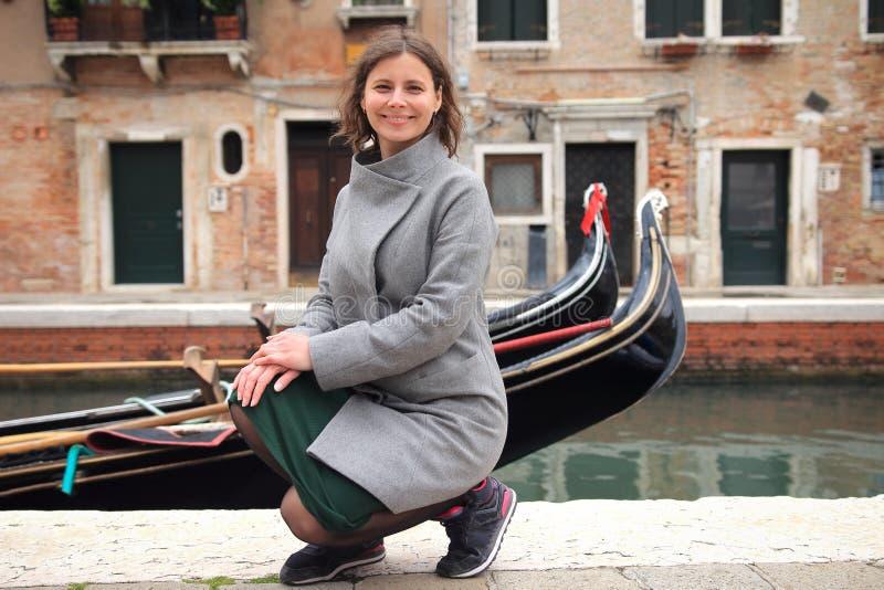 Kvinna i Venedig, Italien Gullig le flicka p? den venetian kanalen med gondoler Lycklig ung kvinna i Venedig arkivfoton