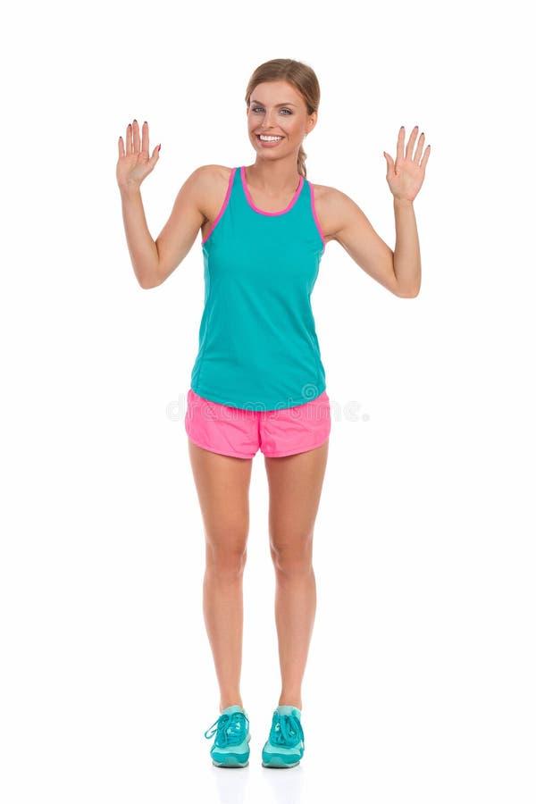 Kvinna i vibrerande sportkläder som visar tio fingrar arkivfoto