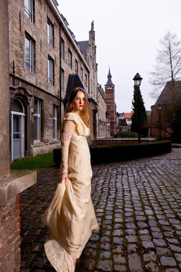 Kvinna i viktoriansk klänning i en gammal stadsfyrkant i aftonen i profil arkivfoto