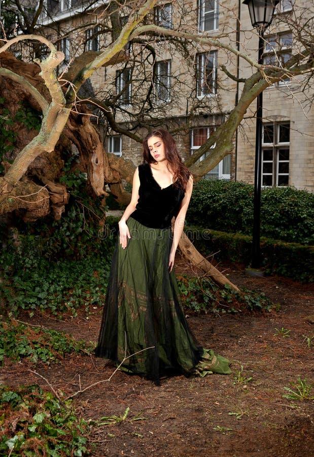 Kvinna i viktoriansk klänning i parkera royaltyfri fotografi