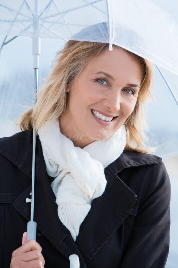 Kvinna i vinter med ett paraply arkivfoto