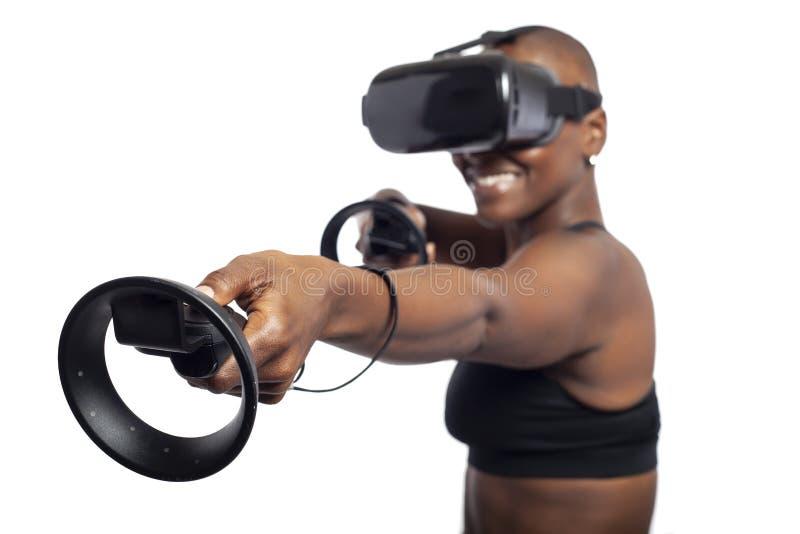 Kvinna i virtuell verklighet som rymmer VR-trollstäver eller kontrollanter royaltyfri bild
