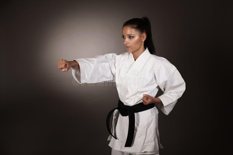 Kvinna i vit kimonostansmaskin hårt i luften - en karatekampsportflicka arkivfoto