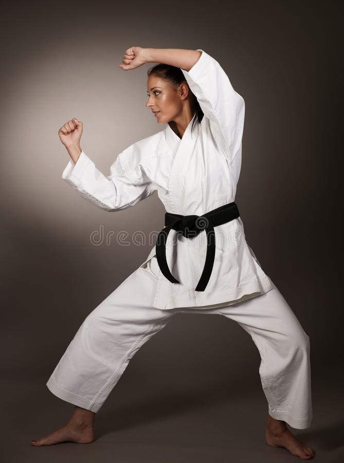 Kvinna i vit kimonostansmaskin hårt i luften - en karatekampsportflicka royaltyfri foto