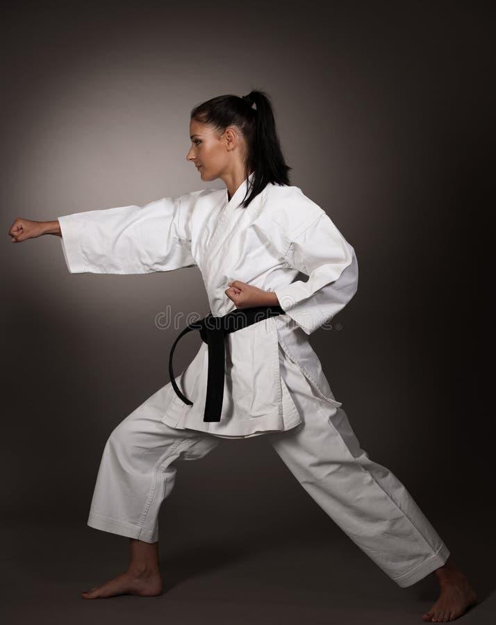 Kvinna i vit kimonostansmaskin hårt i luften - en karatekampsportflicka fotografering för bildbyråer