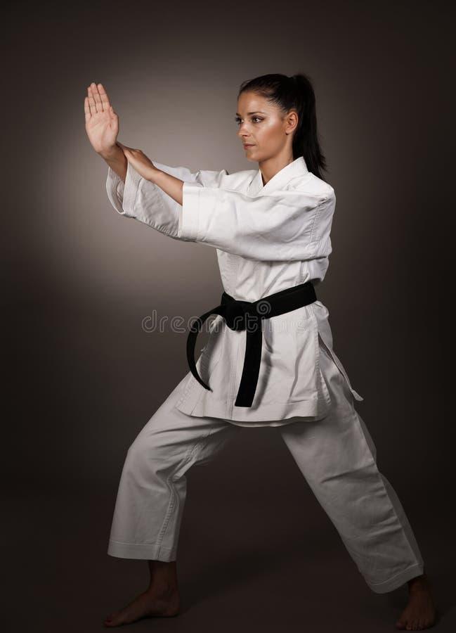 Kvinna i vit kimonostansmaskin hårt i luften - en karatekampsportflicka arkivfoton