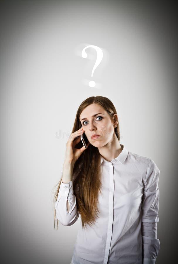 Kvinna i vit med telefonen den frågade vanliga isolerade frågan för begreppsfaq questions white arkivbild