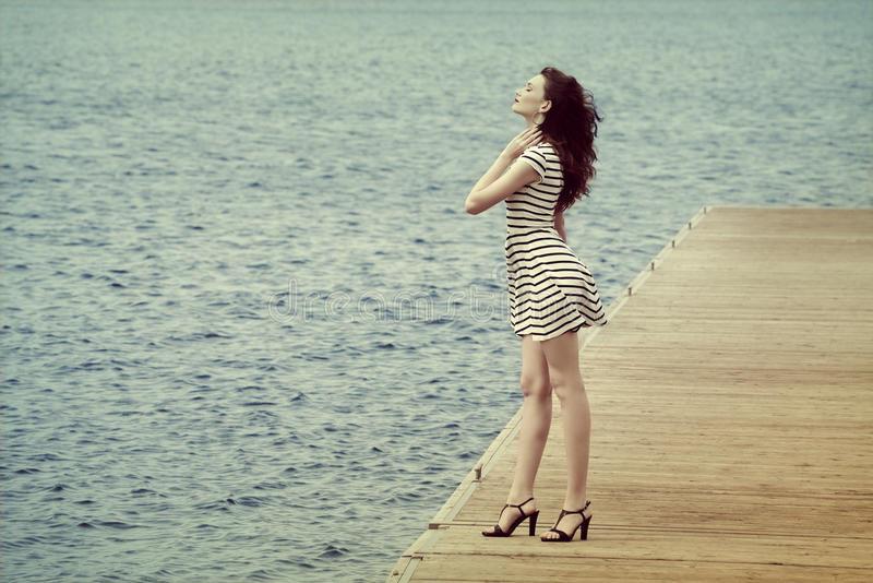 Kvinna i vit på sjösidan fotografering för bildbyråer