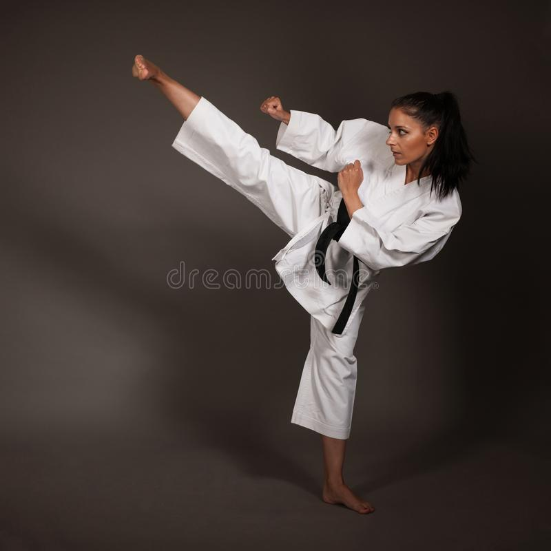 Kvinna i vita kimonosparkar som är höga i luften - en karatekampsportflicka fotografering för bildbyråer