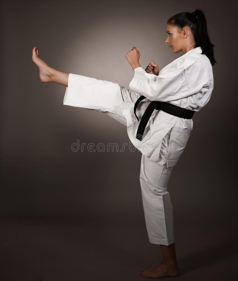 Kvinna i vita kimonosparkar som är höga i luften - en karatekampsportflicka royaltyfria bilder