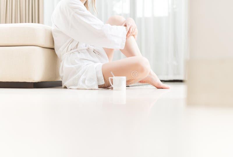 Kvinna i vitt badrocksammanträde på golv. royaltyfri fotografi