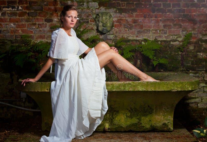 Kvinna i vitt klänningsammanträde på en stenbänk royaltyfri fotografi
